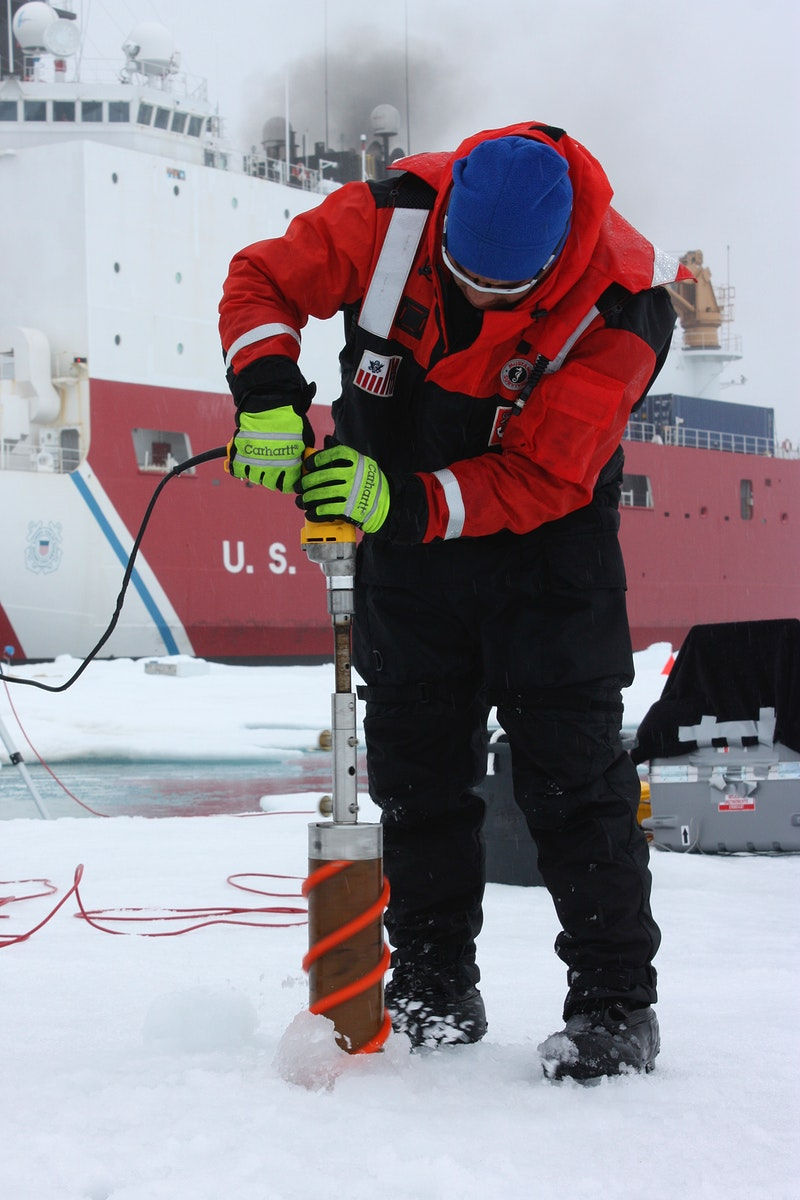 Benny Hopson from the Barrow Arctic Science Consortium in Alaska drills a core sample from sea ice in the Chukchi Sea on July…