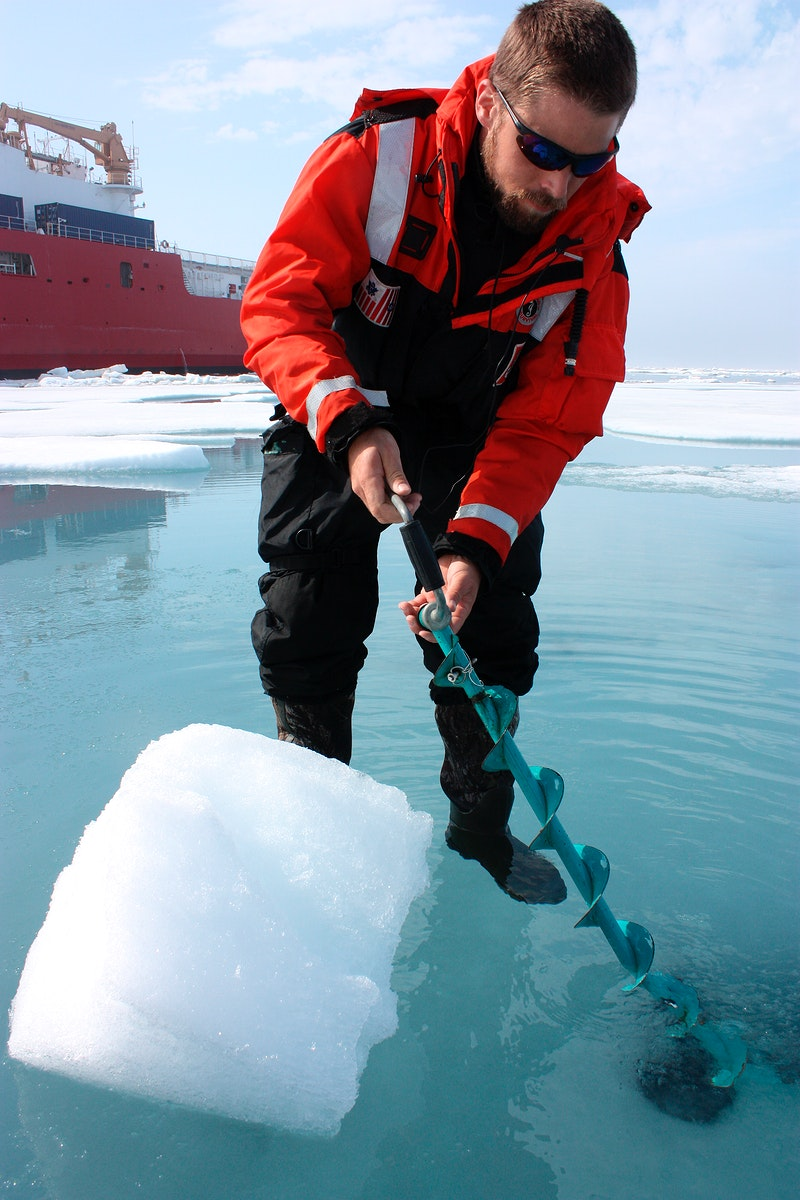 Dartmouth College's Chris Polashenski cuts a block of ice from below a melt pond on sea ice in the Chukchi Sea on July 9…
