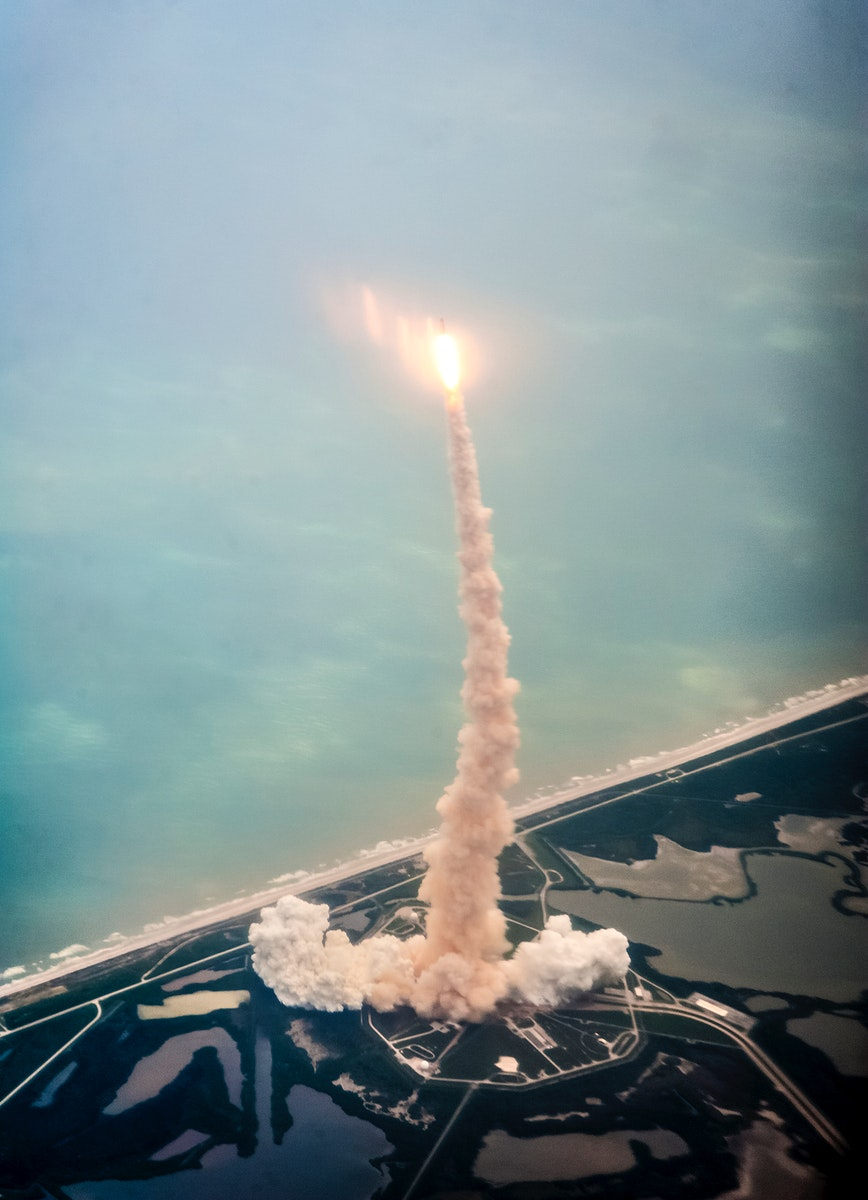 Space shuttle Atlantis is seen through the window of a Shuttle Training Aircraft (STA) as it launches from launch pad 39A at…