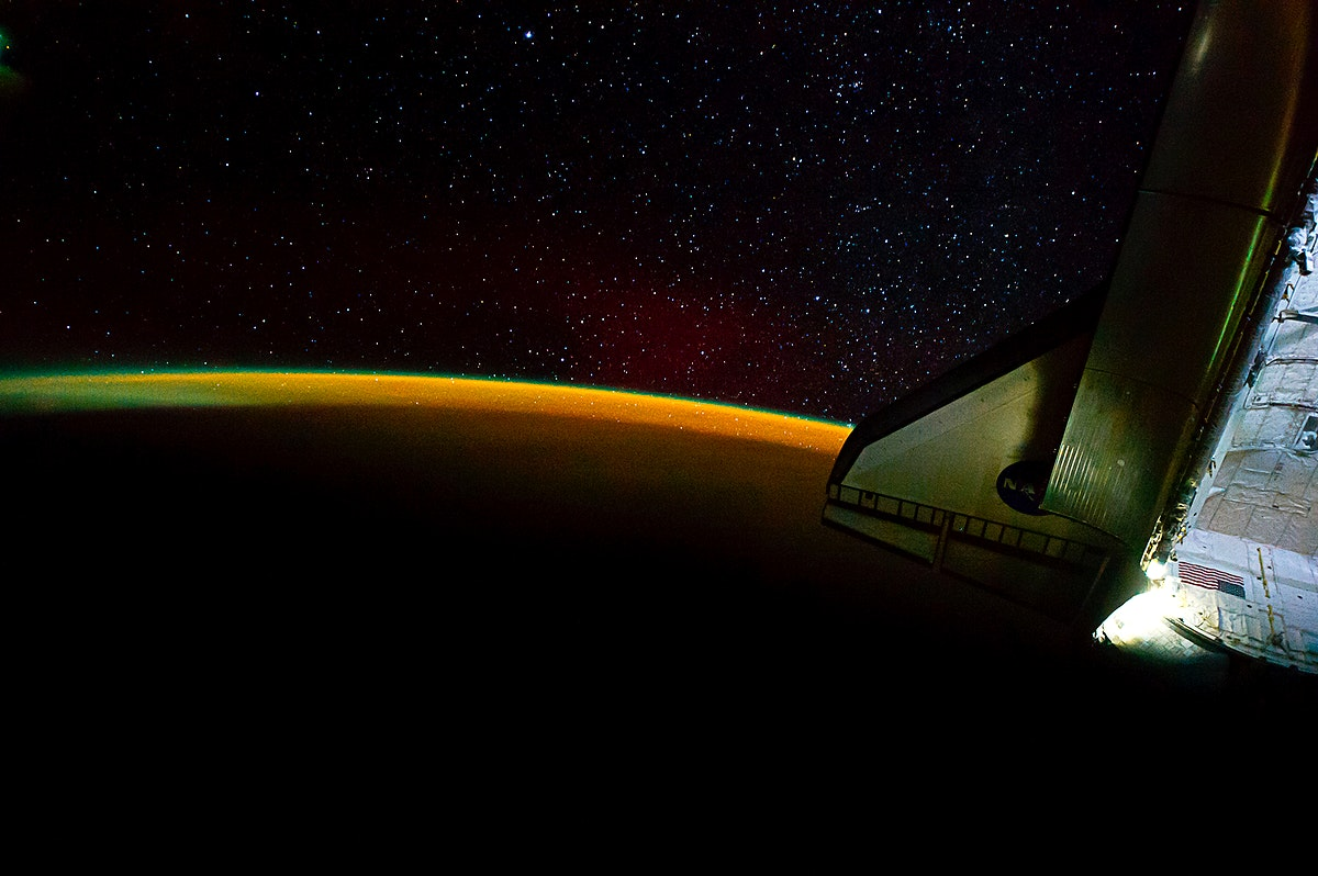 Earth's thin line of atmosphere and a starry sky just off the port wing of the docked space shuttle Endeavour are…