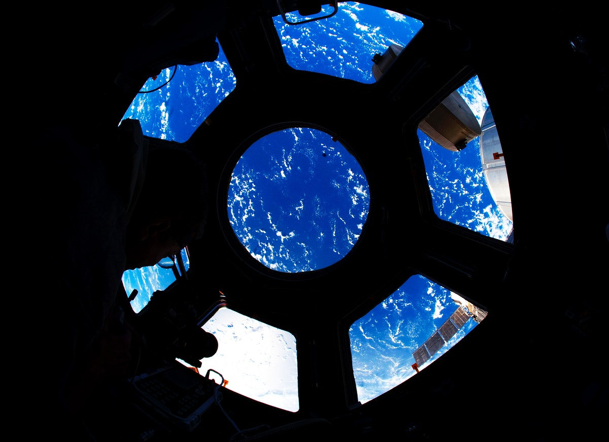 A blue and white part of Earth is visible through the windows in the Cupola of the International Space Station, 22 August…