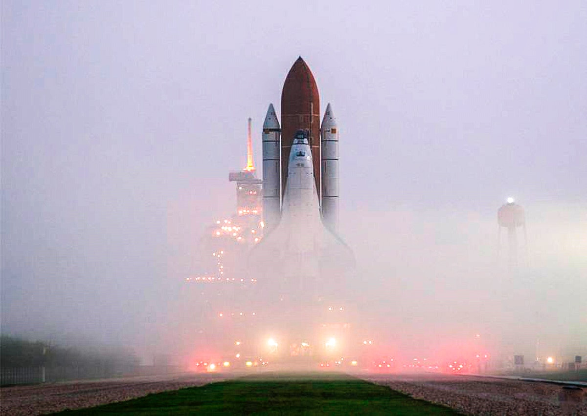 KENNEDY SPACE CENTER, FLA. the fog on Launch Pad 39B is pierced by lights on vehicles and the service structures as Space…