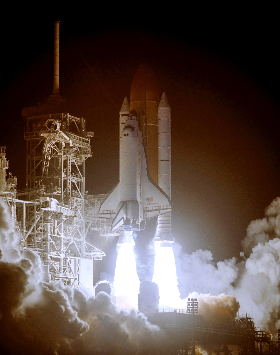 Space shuttle Discover standing on the fiery columns erupting from the solid rocket boosters as it lifts off Launch Pad 39B…