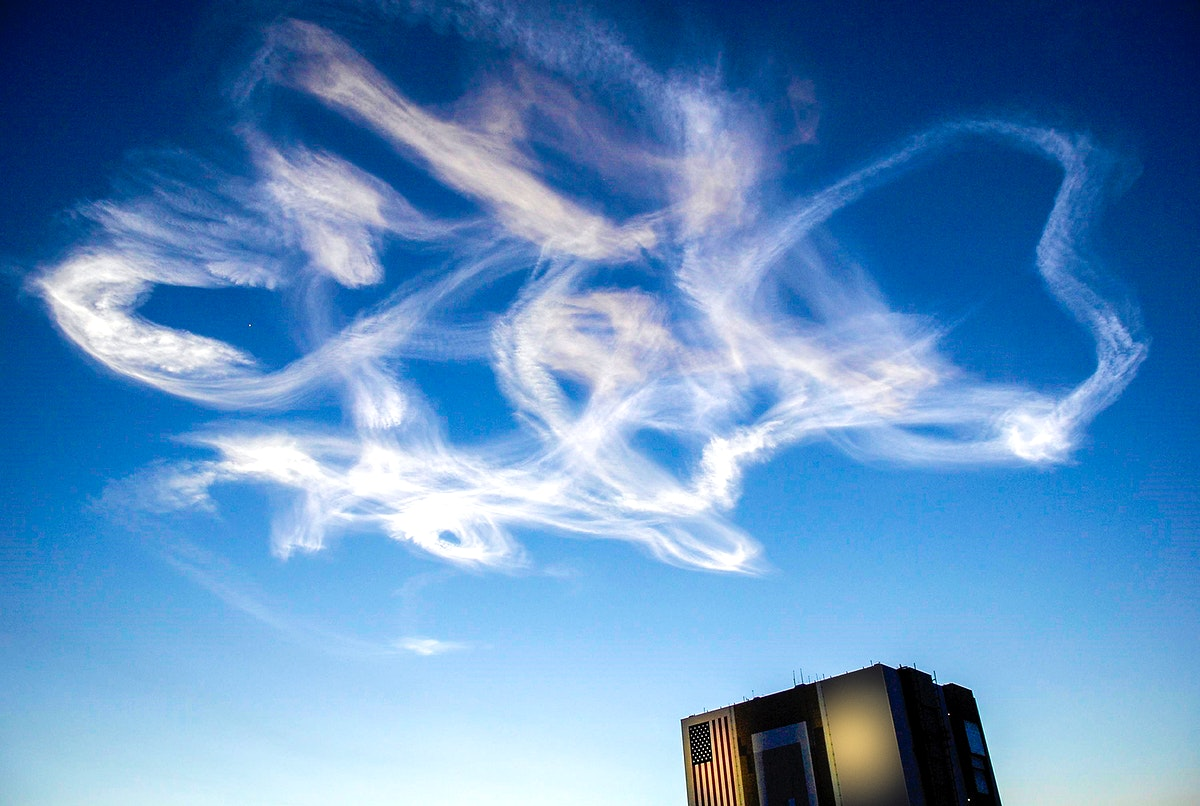 A drifting smoke plumes from the launch of Space Shuttle Atlantis appear to swirl above the Vehicle Assembly Building near…