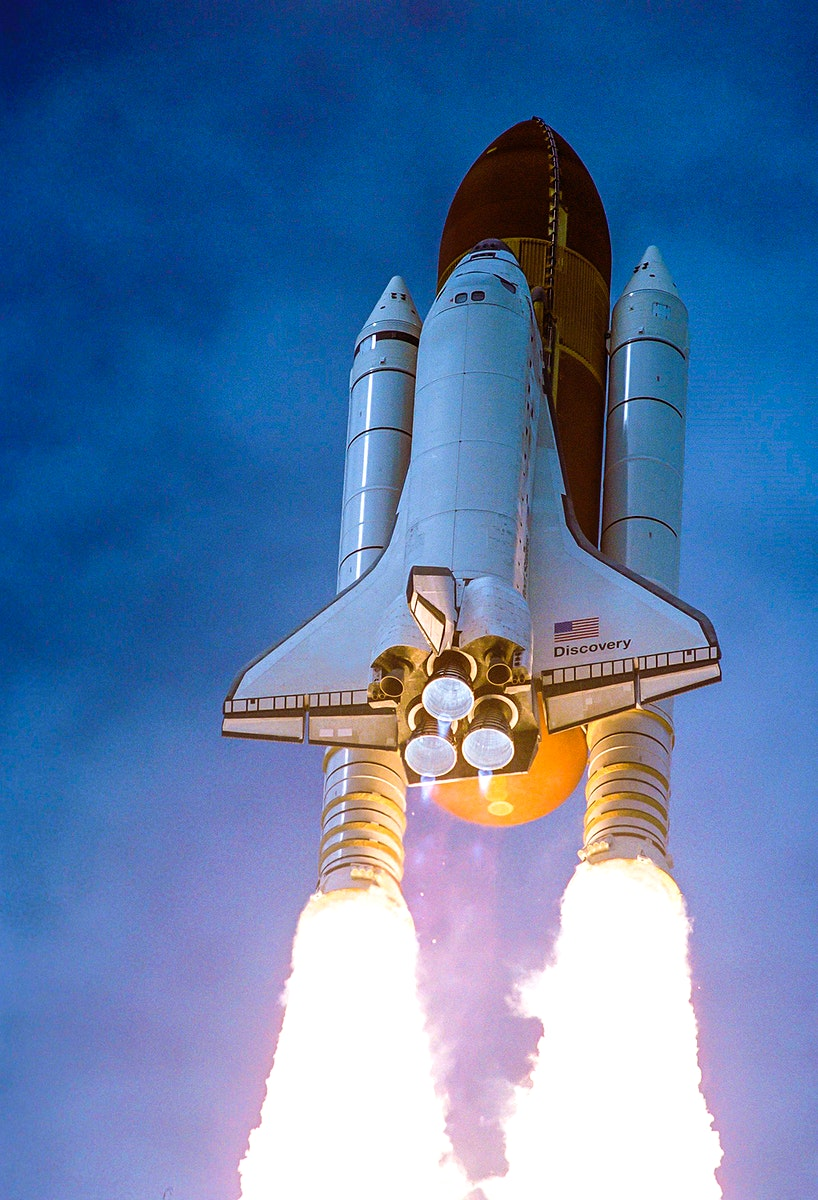 Spewing twin columns of fire from the solid rocket boosters as space shuttle Discovery roars into the blue Florida sky toward…