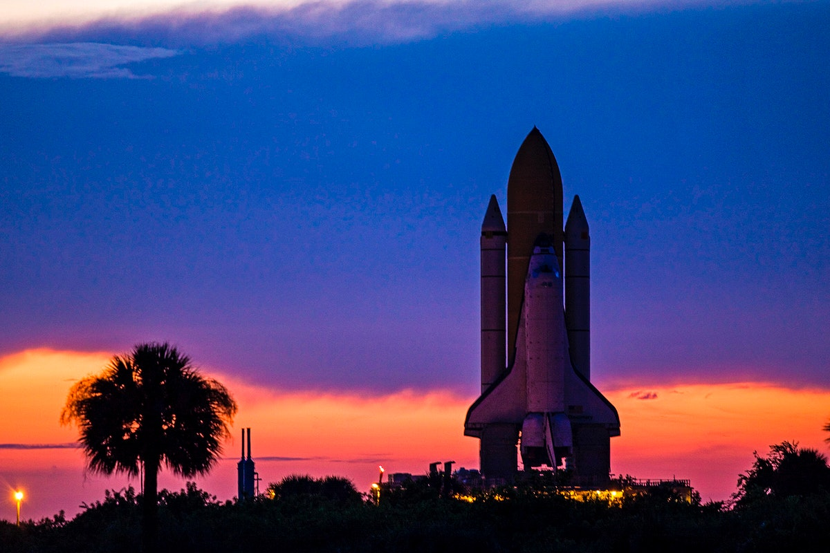 Space shuttle Discovery is silhouetted against the dawn sky as it rolls out to Launch Pad 39A at NASA's Kennedy Space Center…