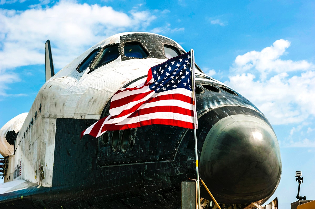 An American flag flaps proudly in the wind in front of space shuttle Atlantis on the Shuttle Landing Facility's Runway 15 at…