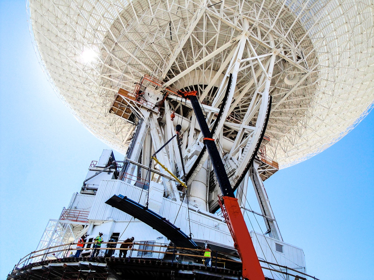 Under the unflinching summer sun, workers at NASA's Deep Space Network complex in Goldstone, Calif., use a crane to lift a…