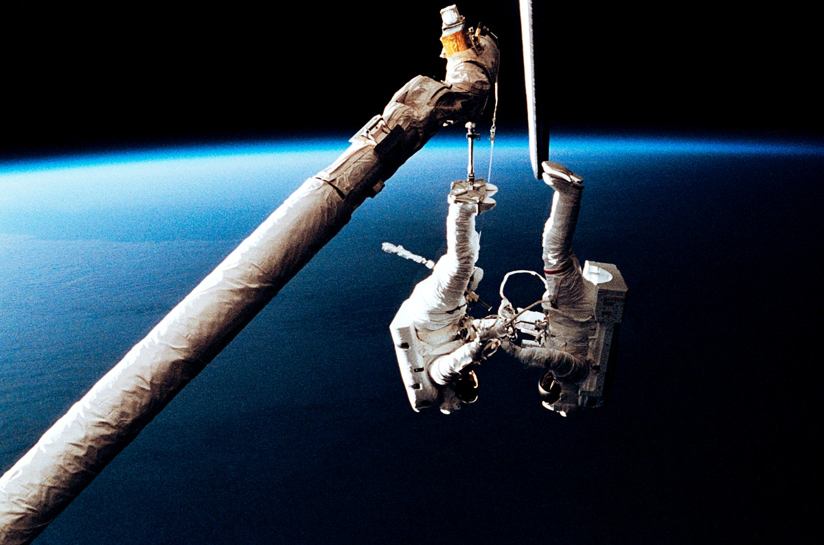 Astronaut Mark C. Lee (right) floats freely as he continues to test the new Simplified Aid for EVA Rescue (SAFER) system…