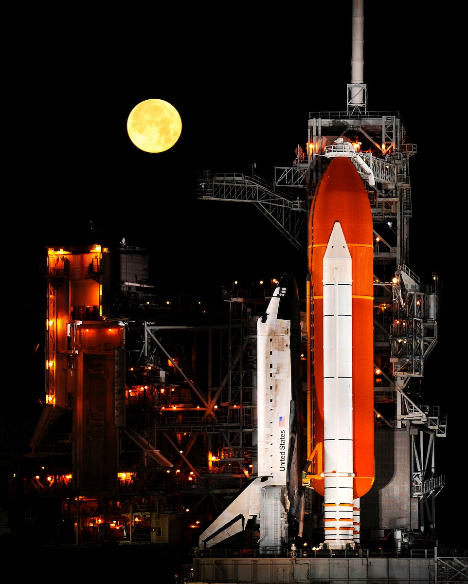 A nearly full Moon sets as the space shuttle Discovery sits atop Launch pad 39A at the Kennedy Space Center in Cape…