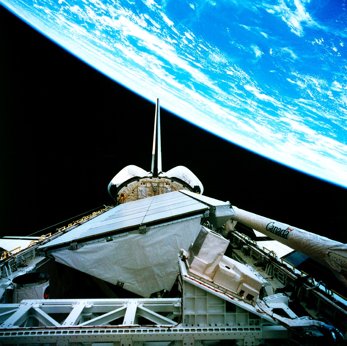 The payload bay of the orbiting space shuttle Endeavour with an area of the Pacific Ocean northeast of Hawaii in the…