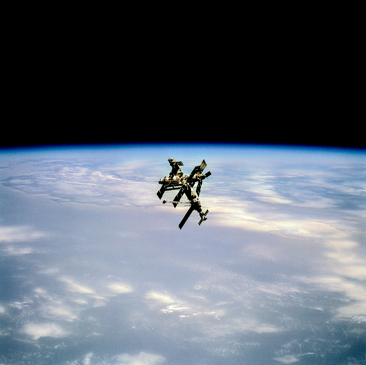Russia's Mir Space Station is backdropped against blue and white Earth near its horizon, 29 June 1995. Original from NASA .…