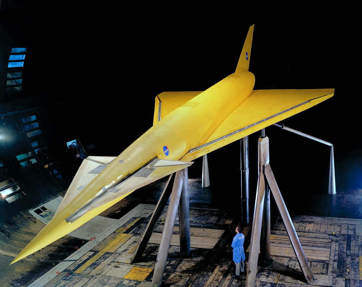 Hypersonic Transport Model. High 3/4 top front view of model in Ames 40x80 foot wind tunnel. Bob Bishop in lower right. Delta…