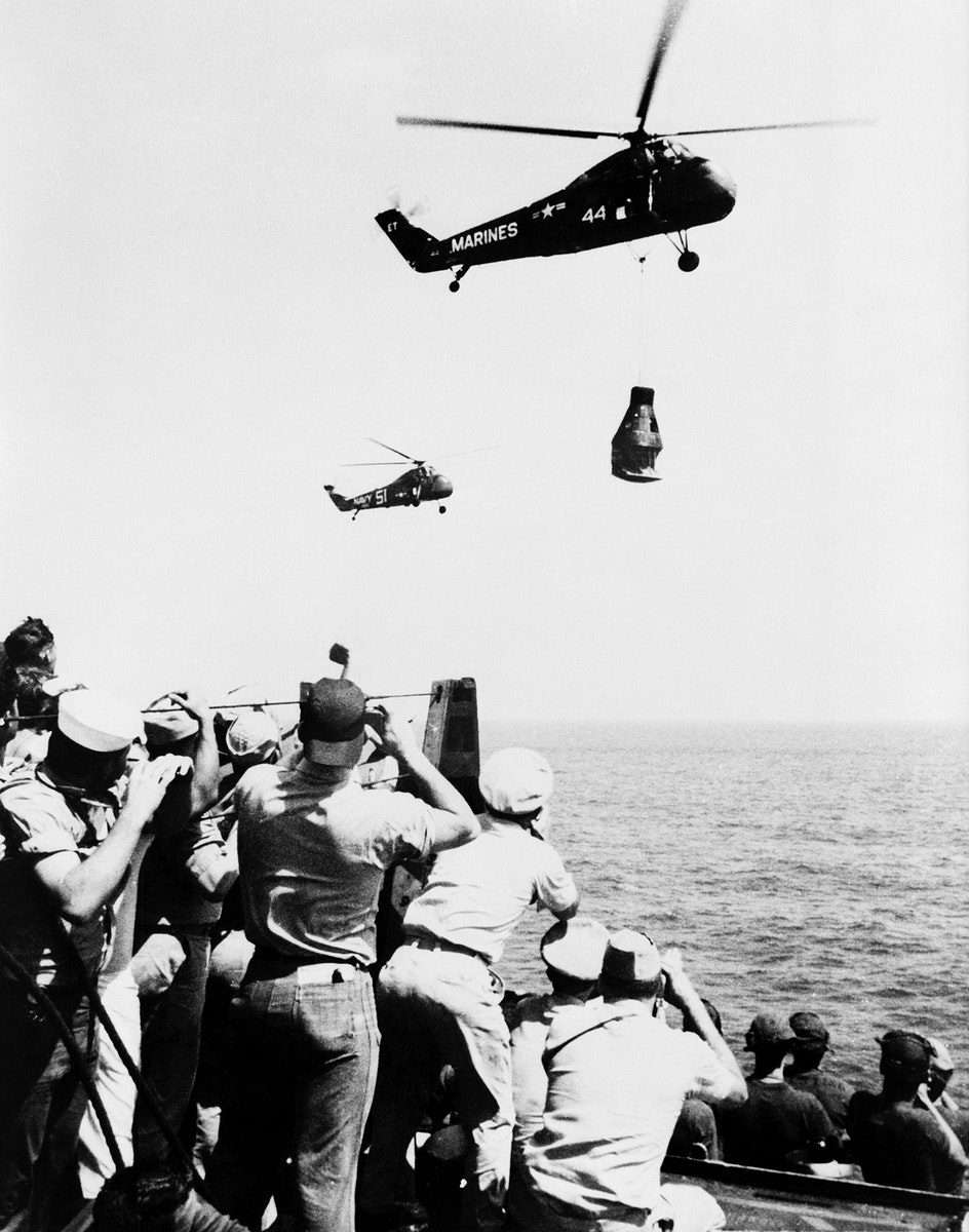 Crew members of the U.S. Navy Carrier Champlain cheer and take pictures of the arrival of the first Project Mercury pilot.…