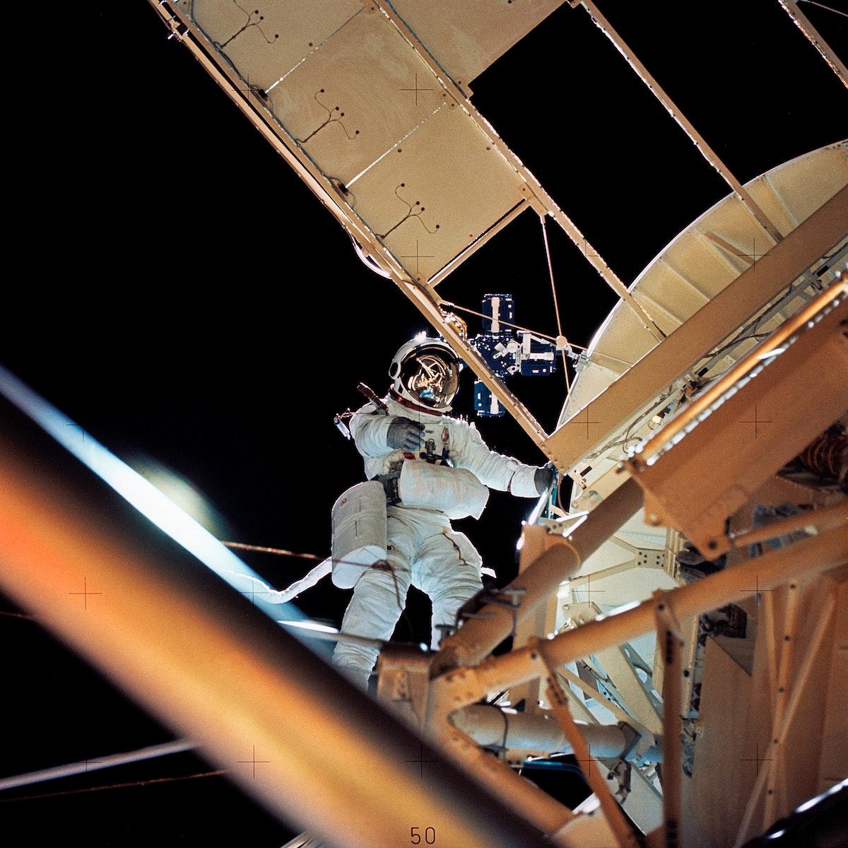 Astronaut Owen K. Garriott, Skylab 3 science pilot, retrieves an imagery experiment from the Apollo Telescope Mount (ATM)…