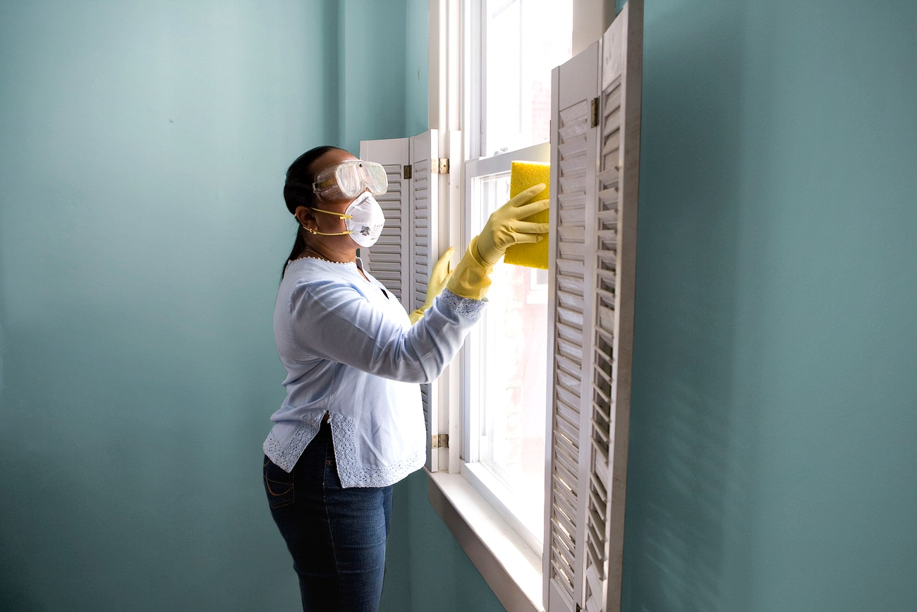 Woman using a damp sponge to clean dust collected on a window sill. Original image sourced from US Government department:...