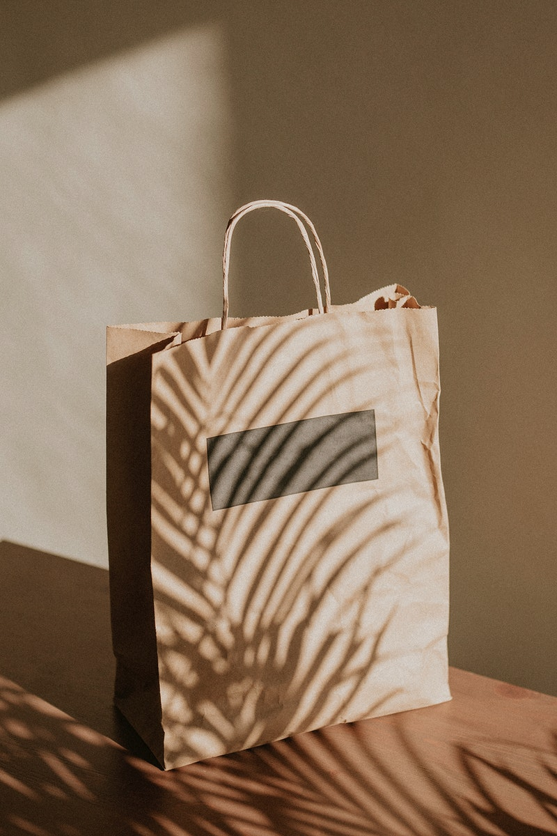 Natural paper bag with palm leaves shadow
