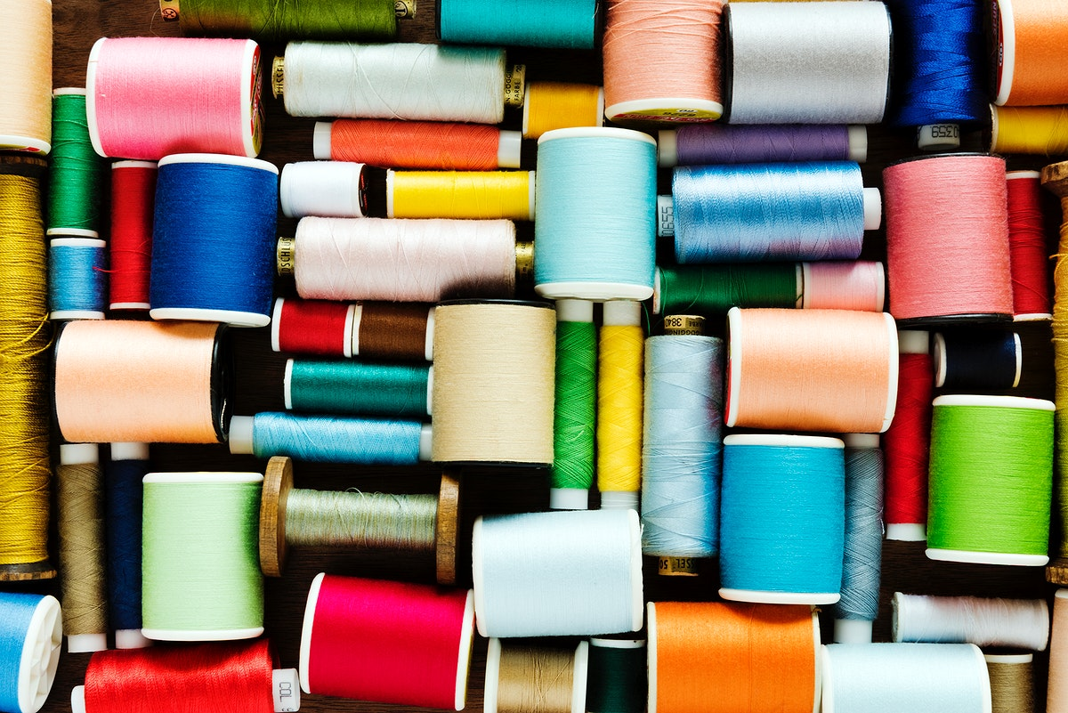 Colorful sewing threads background closeup