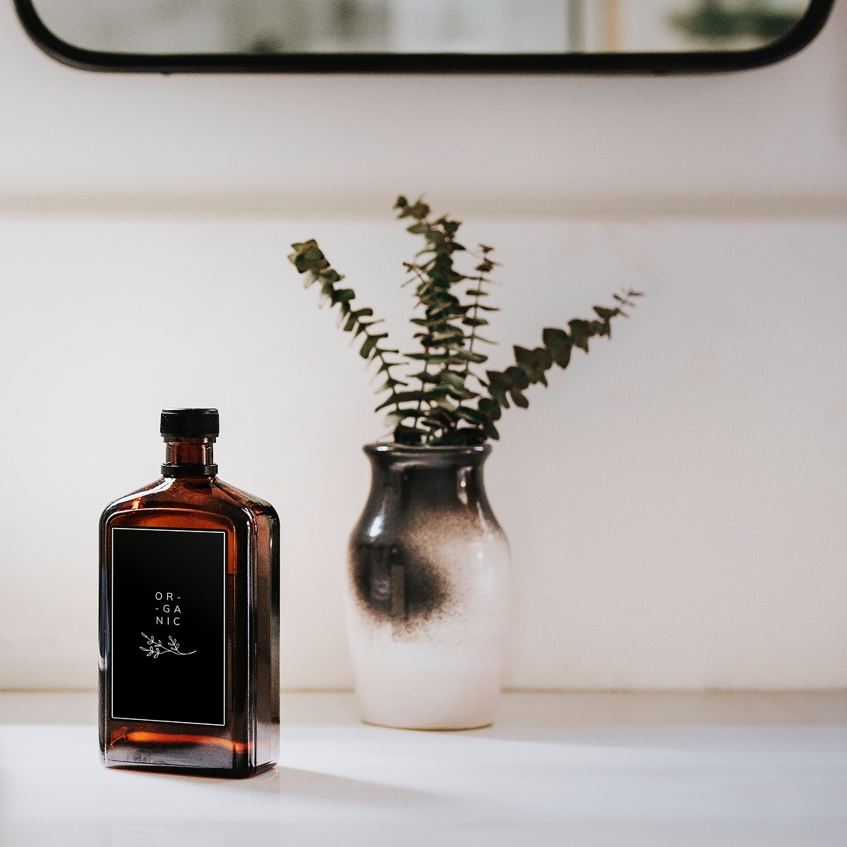 Liquid brown bottle mockup by a vase