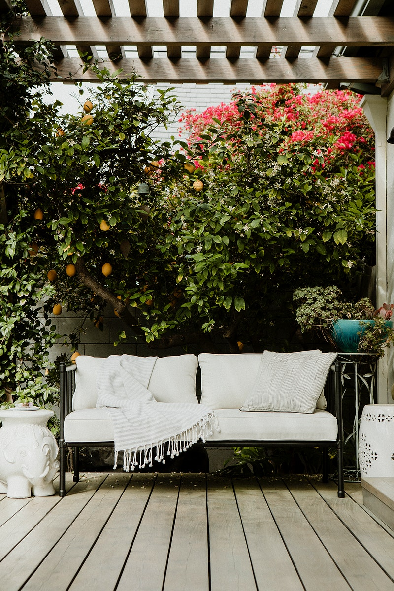 Outdoor wooden couch with white cushions