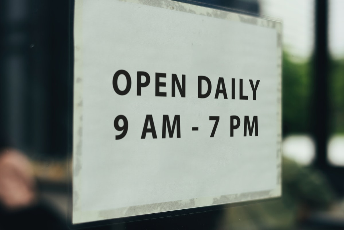 Shop open hours signboard on a window