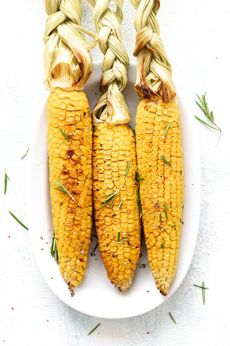 Fresh corn on the cob with organic rosemary leaves