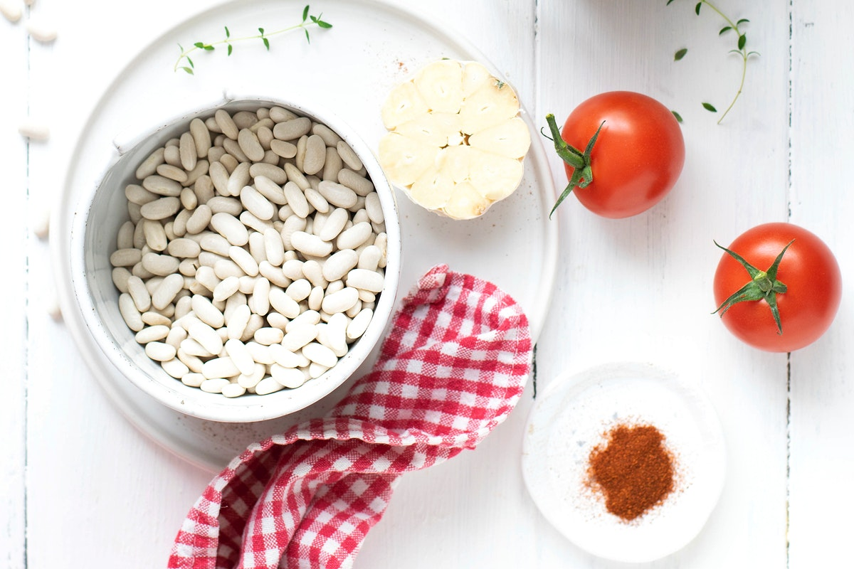 Raw white beans in a bowl by sun-dried tomatoes