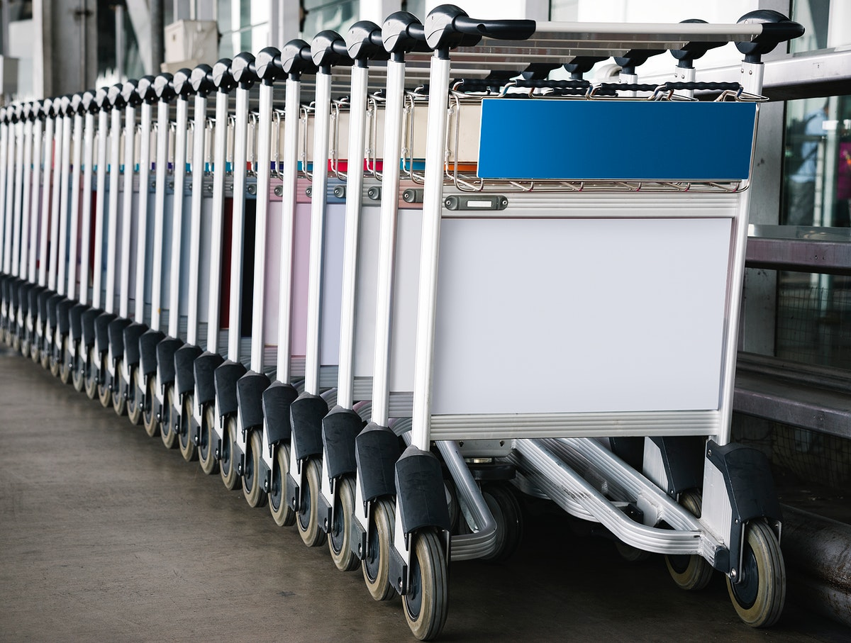 Luggage trolley at the airport with sign mockup