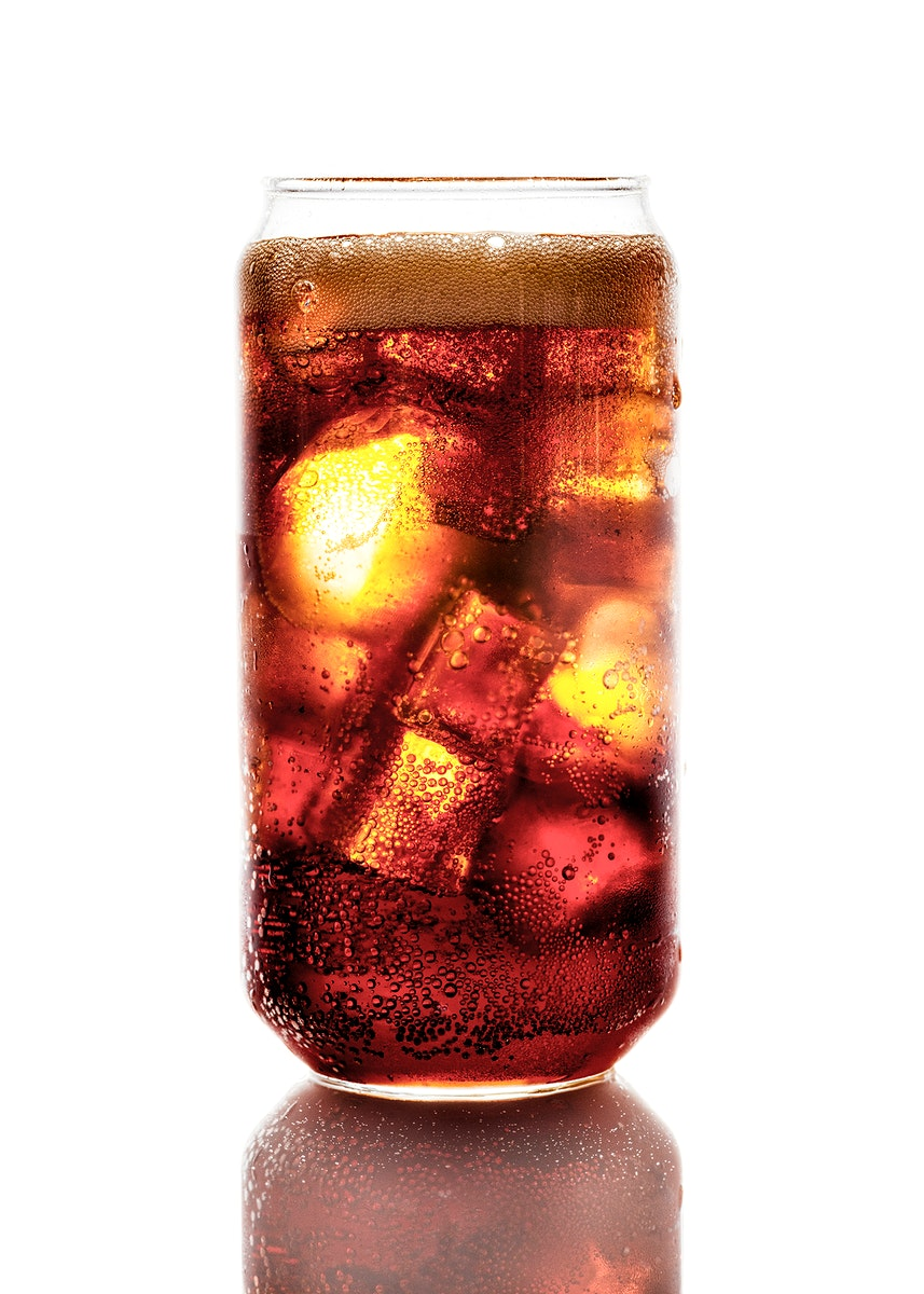 Cold carbonated drink over ice cubes in a can shaped glass
