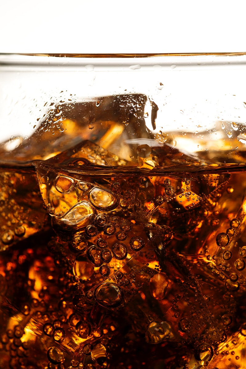 Cold carbonated drink over ice cubes in a glass close up
