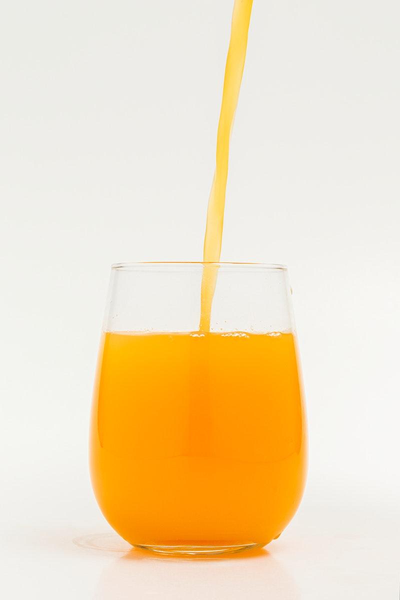 Pouring fresh organic orange juice into a glass