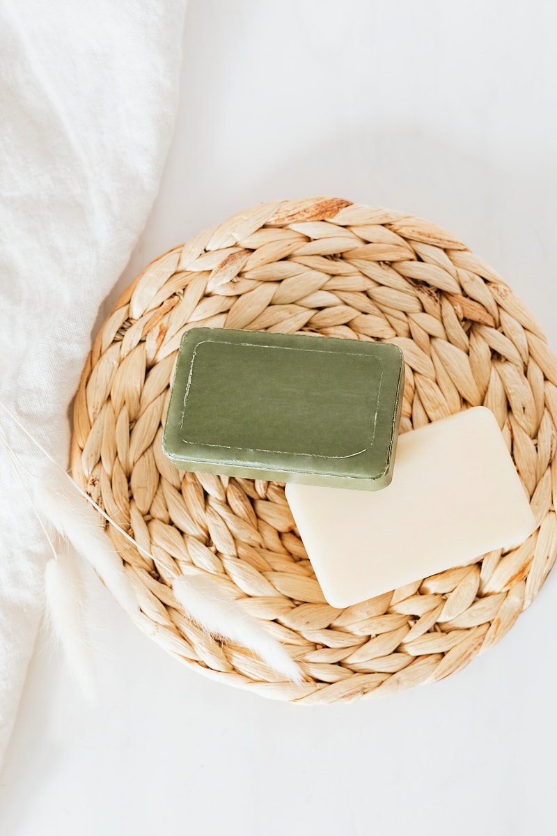 Flat lay organic soap bars with grass flowers in spa setting
