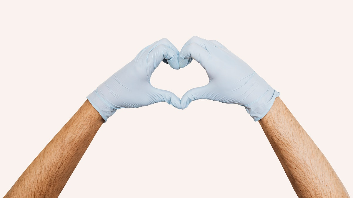 Gloved hands making a heart shaped sign on a beige background