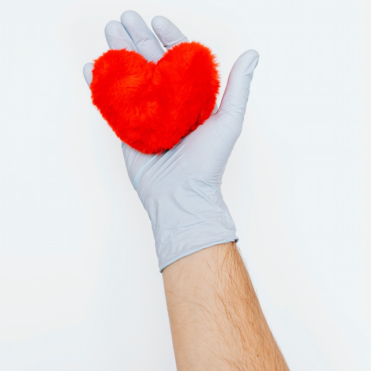 Gloved hand holding a fluffy red heart