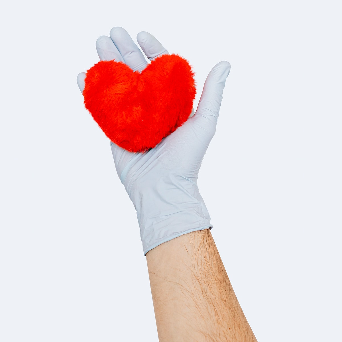 Gloved hand holding a fluffy red heart mockup