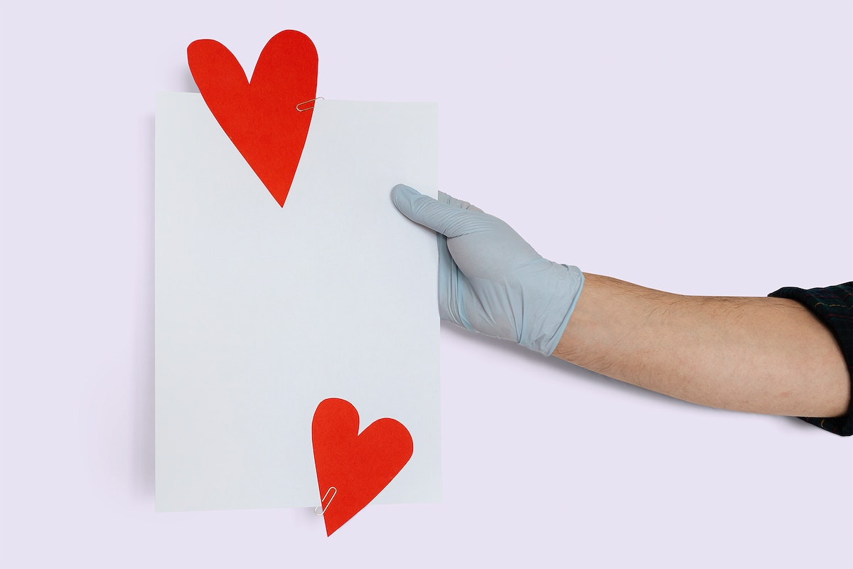 Gloved hand holding a card mockup decorated with red hearts