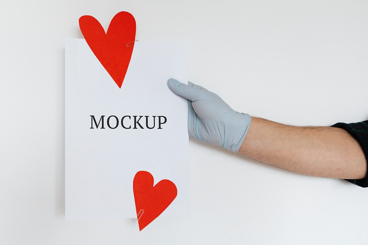 Gloved hands holding a card mockup decorated with red hearts