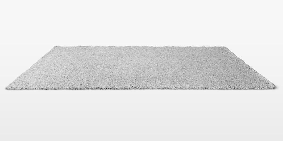 Gray fluffy floor carpet on off white background