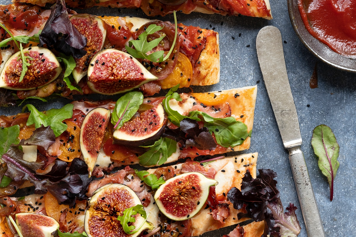 Pizza with tomatoes ham mozzarella and figs flat lay sliced up