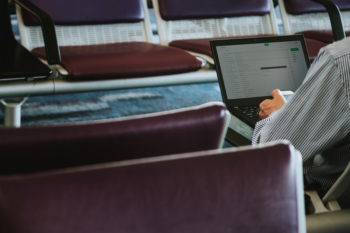 Man using a laptop on a leather seats in waiting area at the airport