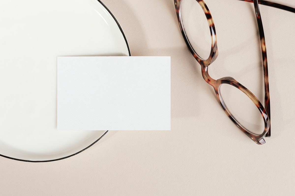 Blank business card on a plate with glasses