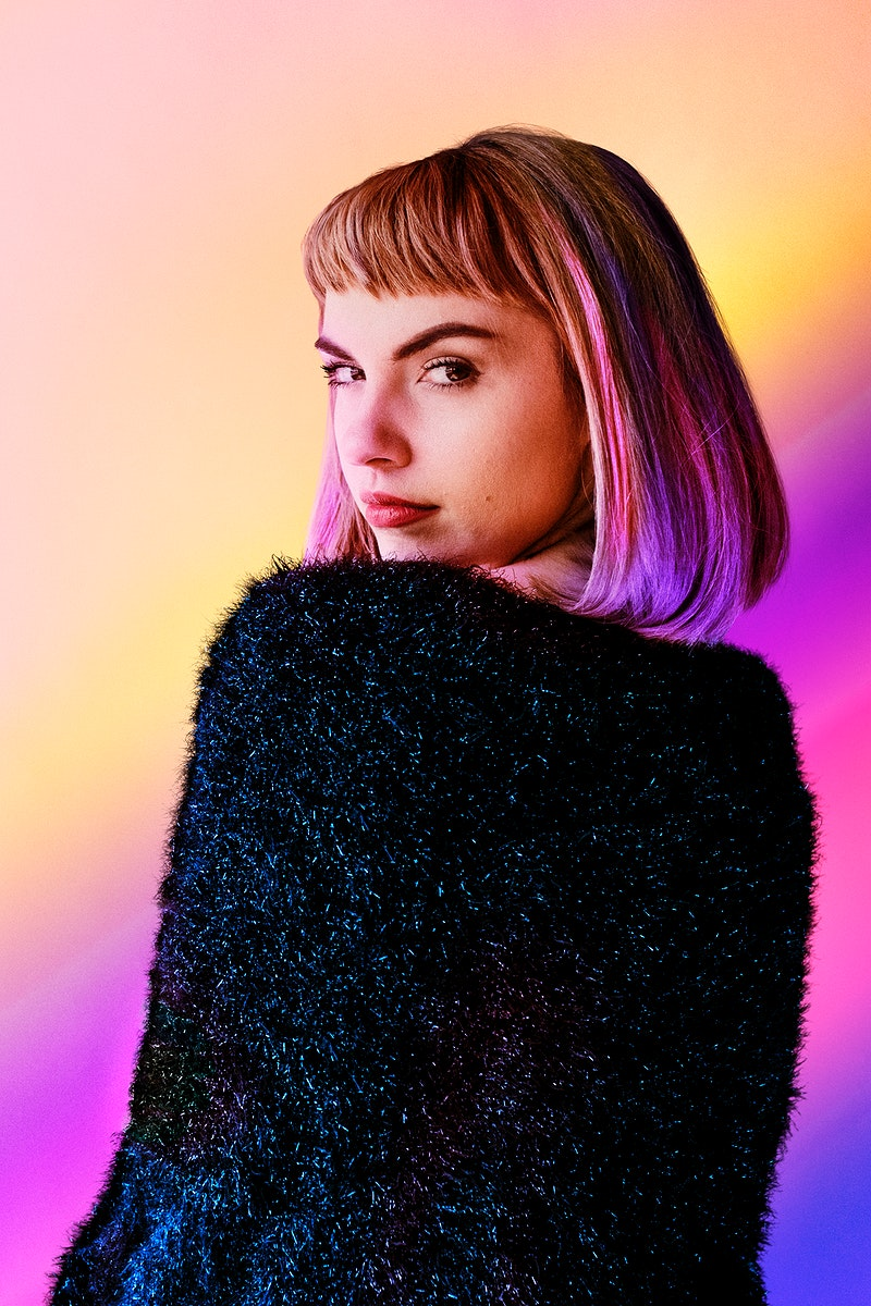 Brown hair woman in a black fluffy sweater looking back over her shoulder
