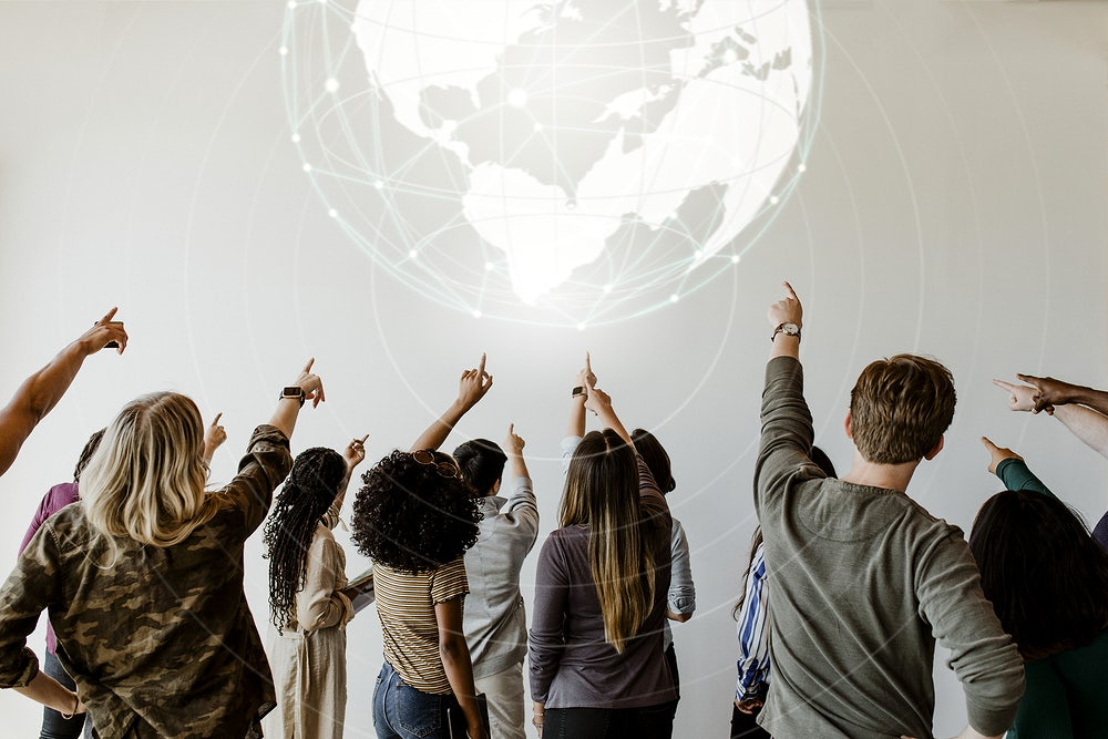 Rearview of diverse people pointing to a global network symbol
