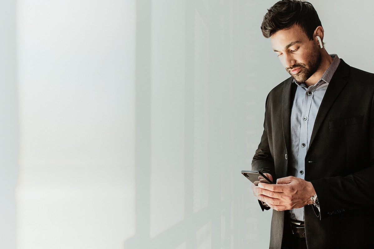 Man in a suit watching an online video from his phone