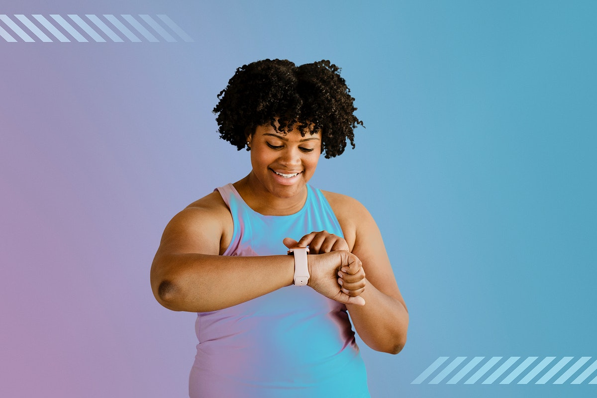 Happy active African American woman using a smartwatch