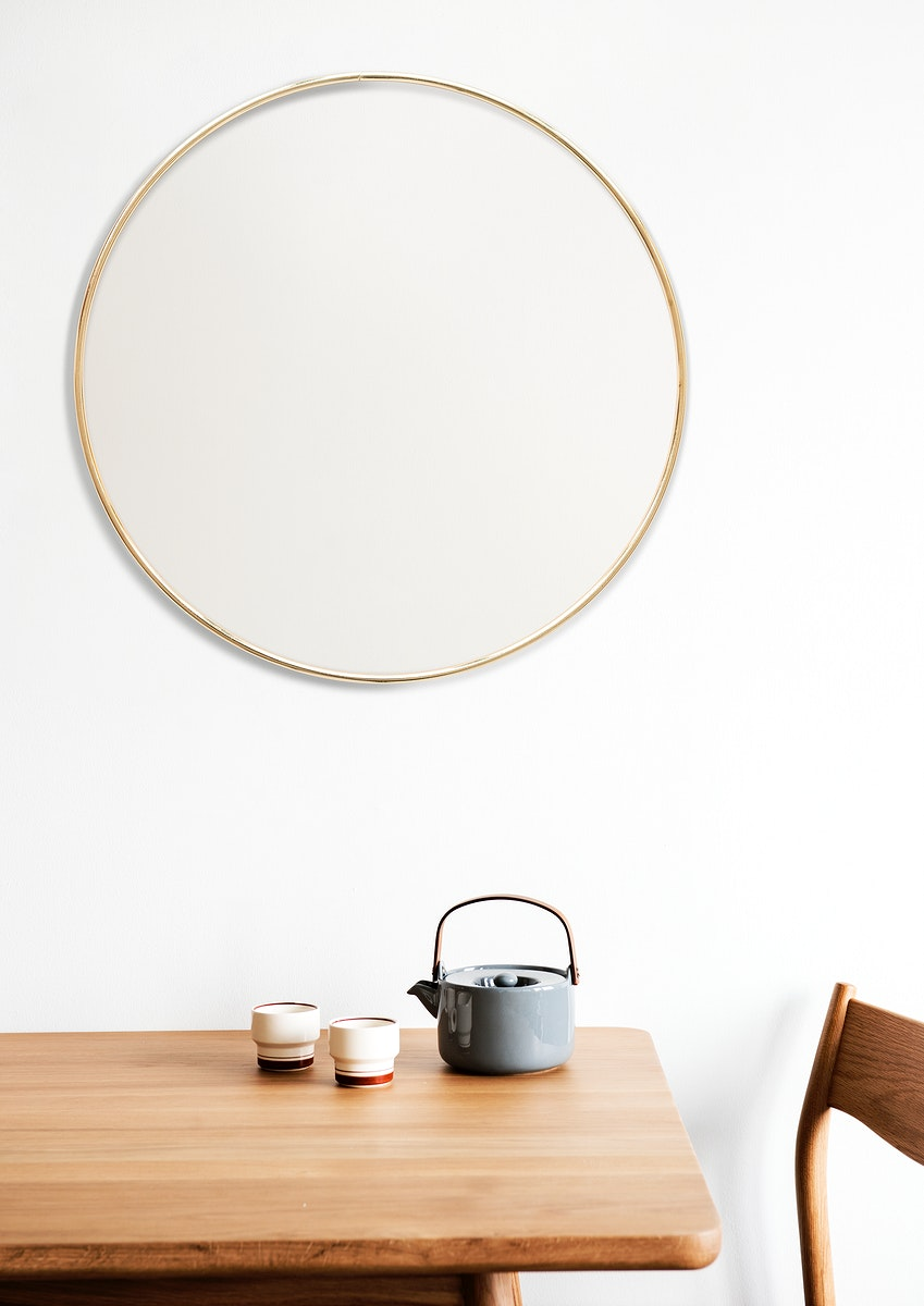 Golden frame on a white wall by a tea set
