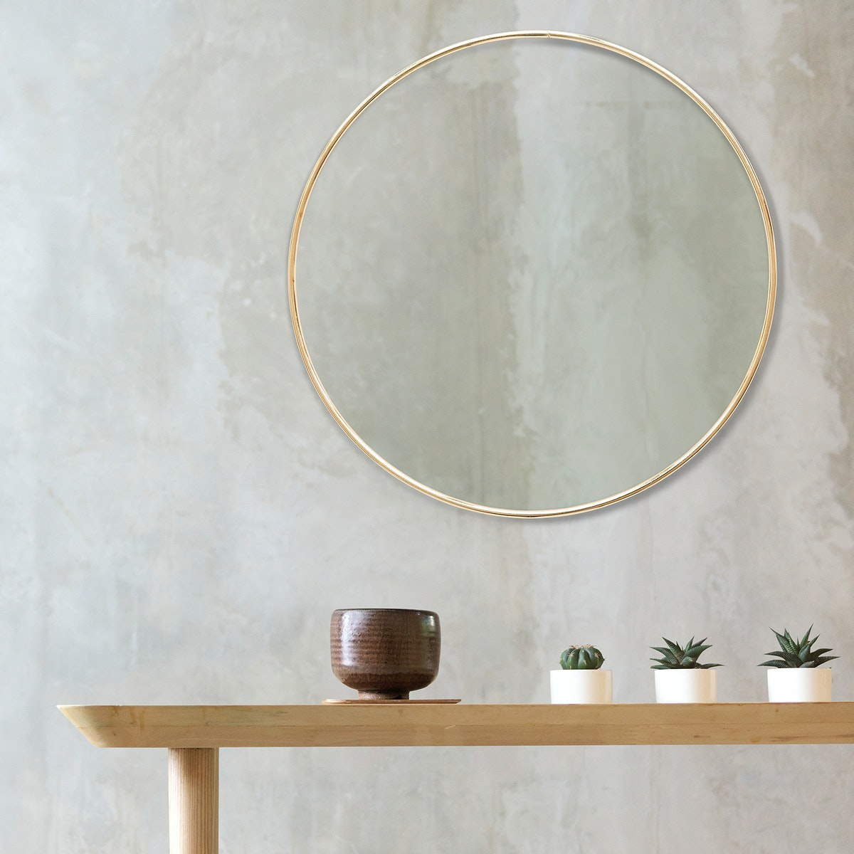 Golden frame on a wall by mini cactuses