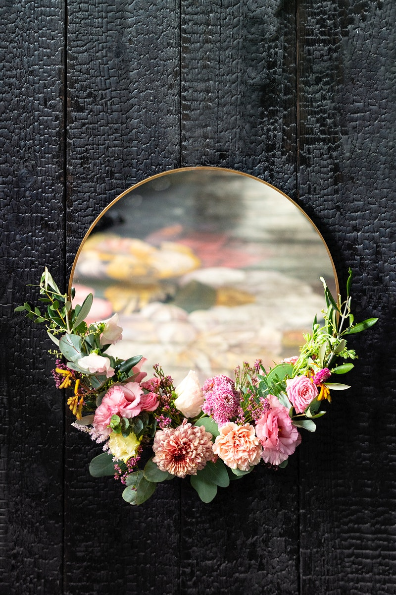 Golden floral framed mirror on a black wall