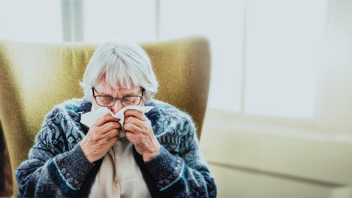 Coronavirus infected senior woman sneezing into a tissue paper social template