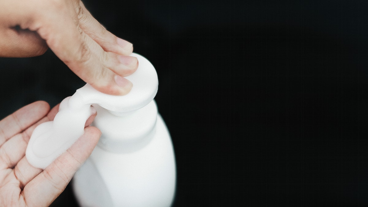 Man cleaning hands with a soap dispenser